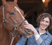 Woman petting a brown horse