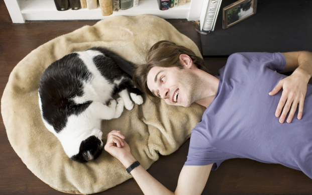 Man laying with black and white cat
