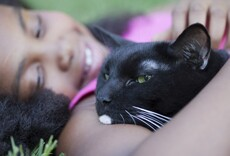 Young girl laying in grass with black cat